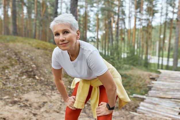 Außenporträt der müden frau mittleren alters in der sportbekleidung, die auf spur im park steht, hände auf ihren schenkeln hält und atem nach langer strecke anhält