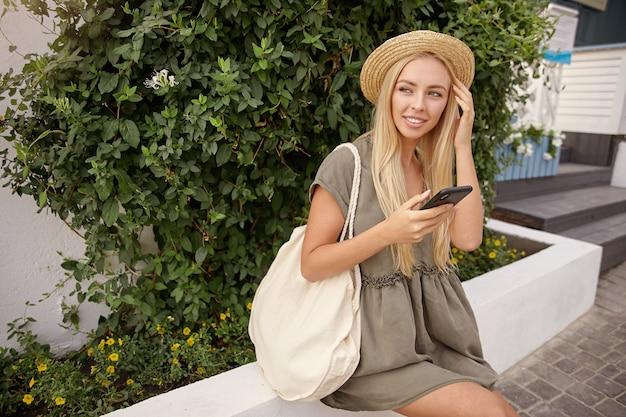 Außenporträt der niedlichen blonden frau mit handy in der hand, die über grünen büschen aufwirft, romantisches leinenkleid und strohhut tragend, mit interesse und sanftem lächeln beiseite schauend
