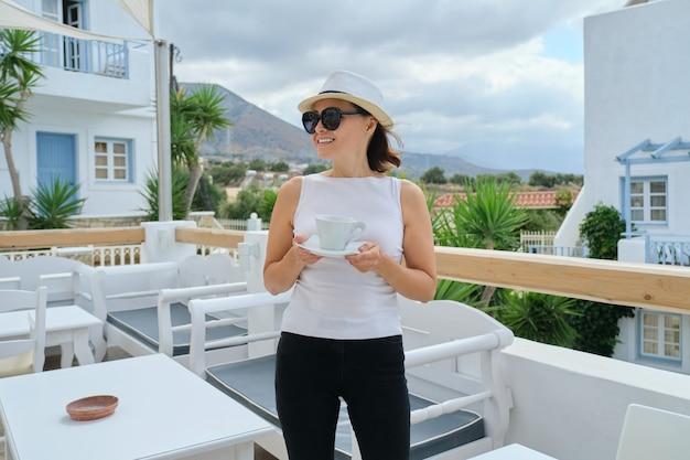 Außenporträt der reifen frau, die im luxus-spa-hotel entspannt, weiblich mit tasse kaffee, die entspannung und landschaft genießt