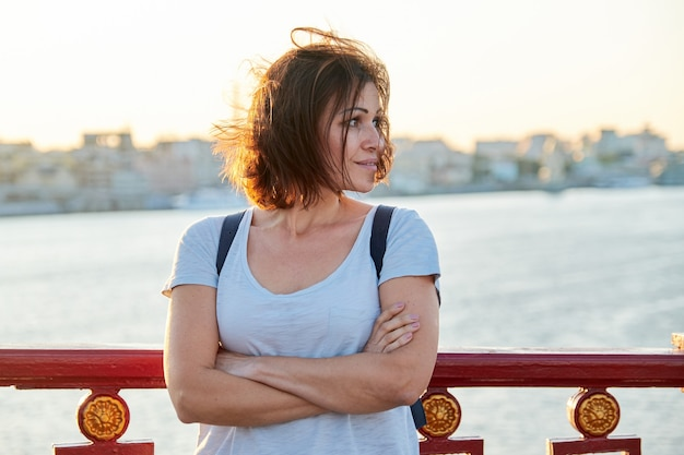 Außenporträt der reifen schönen glücklichen frau mit verschränkten armen, weibliches gehen mit rucksack auf brücke am sommertag, goldene stunde