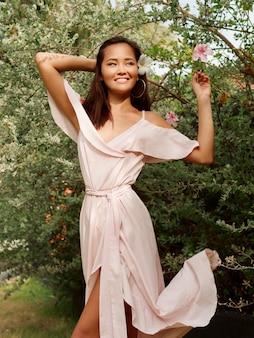 Außenporträt der reizenden glücklichen asiatischen weiblichen aufstellung im sommerpark.