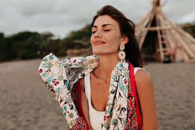 Außenporträt der romantischen entzückenden dame mit den geschlossenen augen, die trendschal und stilvolle einnahmen tragen, die am sonnigen sommertag auf dem strand ruhen