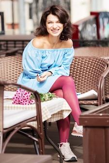 Außenporträt der schönen frau am tisch in einem straßenstadtcafé.