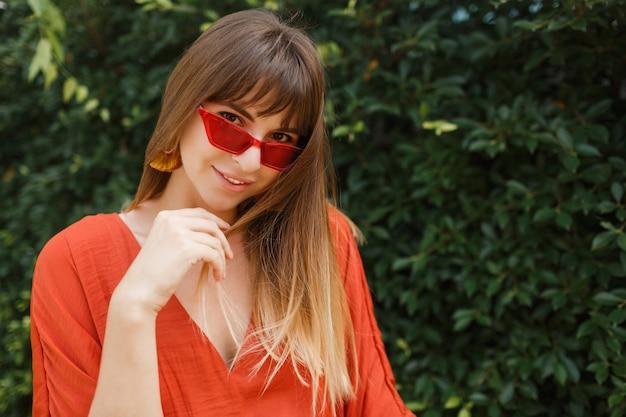 Außenporträt der schönen frau im orangefarbenen kleid und in der roten sonnenbrille.
