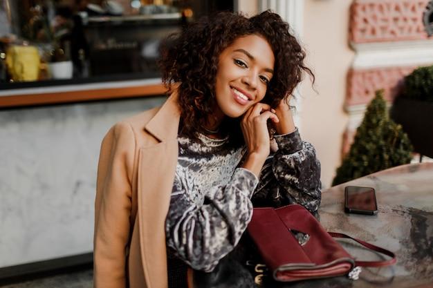 Außenporträt der schönen lächelnden schwarzen frau mit stilvollen afro-haaren, die im café in paris sitzen.