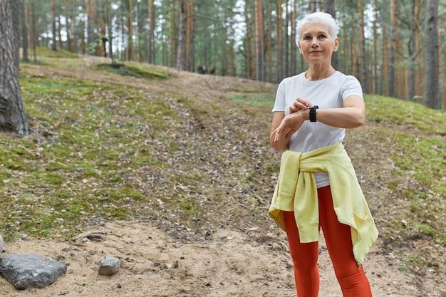 Außenporträt der selbstbewussten aktiven frau mittleren alters in sportbekleidung unter verwendung des intelligenten uhrüberwachungspulses oder der herzfrequenz während des trainings im park.