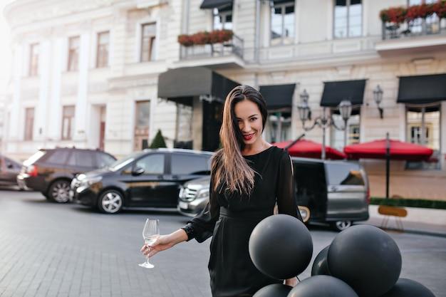 Außenporträt der sorglosen frau, die glas champagner hält, während auf der straße steht