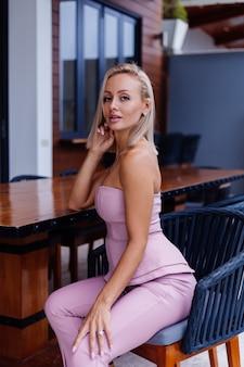 Außenporträt der stilvollen europäischen frau auf rosa modeanzug außerhalb der villa