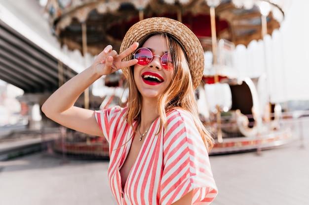 Außenporträt des atemberaubenden mädchens, das mit friedenszeichen nahe karussell aufwirft. weibliches modell mit erfreutem lächeln, das im vergnügungspark tanzt.