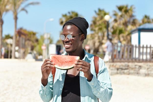 Außenporträt des attraktiven jungen studenten, der scheibe der reifen saftigen wassermelone hält