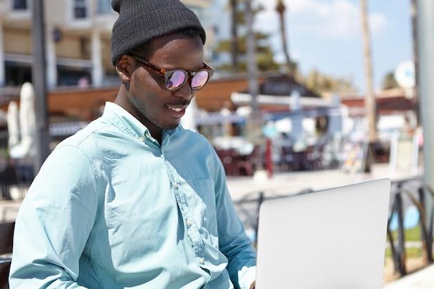 Außenporträt des entspannten jungen mannes in der stilvollen kopfbedeckung und in der sonnenbrille unter verwendung des computers
