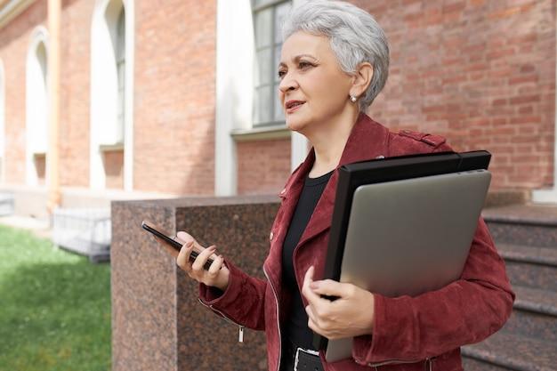 Außenporträt des ernsthaften reifen weiblichen managers, der in eile zum büro ist, im freien mit tragbarem computer aufwirft, taxi online über app auf handy bestellt