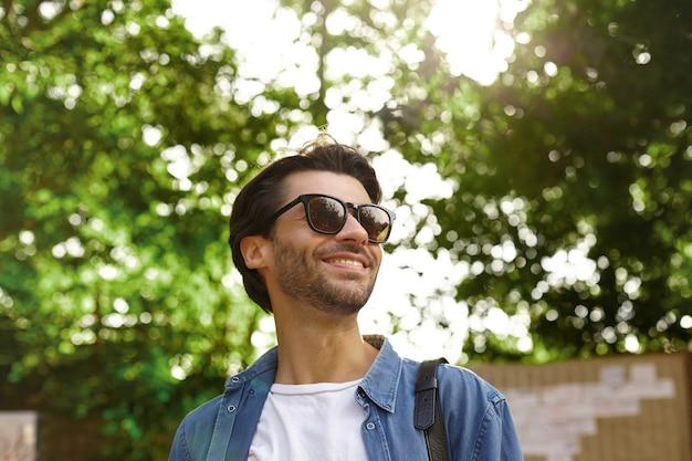 Außenporträt des glücklichen hübschen bärtigen mannes mit dem dunklen haar, das beiseite schaut und fröhlich lächelt und über grünen bäumen an warmem hellem tag aufwirft