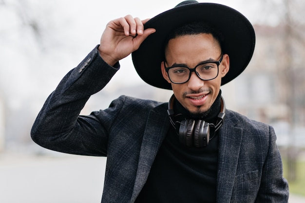 Außenporträt des glückseligen selbstbewussten mannes in der dunklen kleidung. der lächelnde afrikanische junge trägt eine brille, die mit vergnügen auf unschärfe aufwirft.