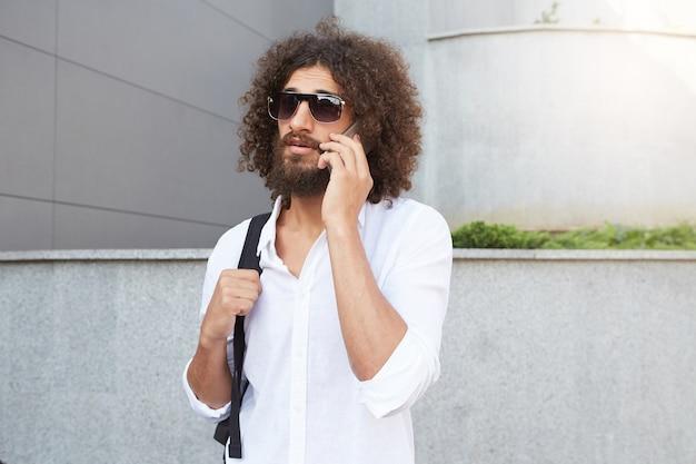 Außenporträt des gutaussehenden gutaussehenden mannes mit dem üppigen bart und den locken, die am telefon sprechen, während sie die straße entlang gehen und freizeitkleidung tragen
