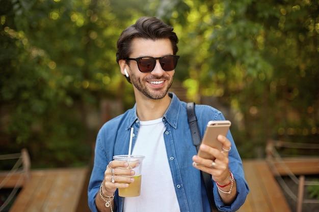 Außenporträt des hübschen dunkelhaarigen mannes mit dem smartphone in der hand, das gute nachrichten liest und gute laune hat, eistee im plastikbecher trinkend