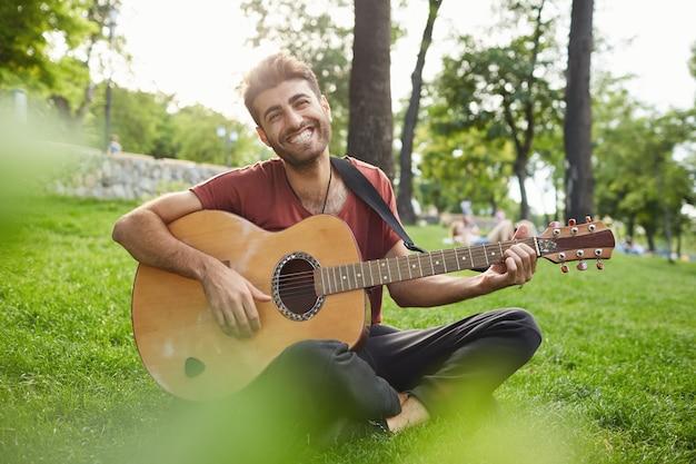Außenporträt des hübschen hipster-mannes, der auf gras im park sitzt und gitarre spielt