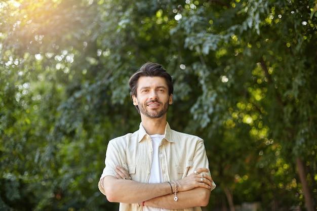Außenporträt des hübschen jungen bärtigen mannes im beige hemd, das mit gekreuzten händen auf seiner brust aufwirft und mit leichtem lächeln schaut