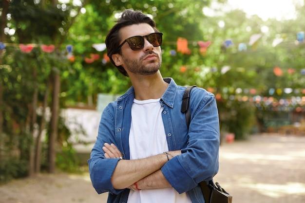 Außenporträt des hübschen jungen bärtigen mannes in der sonnenbrille, die über grünem park mit verschränkten armen auf seiner brust aufwirft und mit ernstem gesicht beiseite schaut