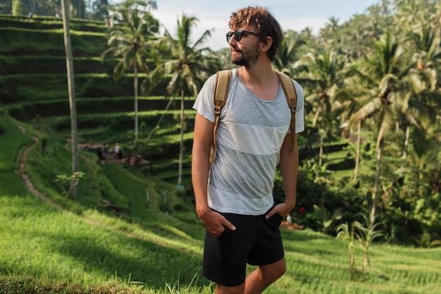 Außenporträt des hübschen reisemannes mit rucksack, der auf aufstiegsterrasse in bali geht.