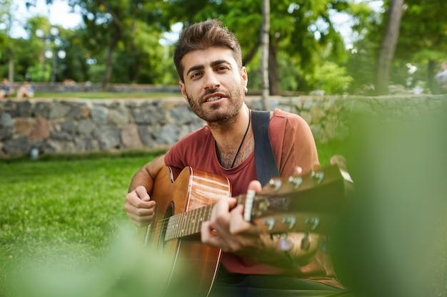 Außenporträt des hübschen romantischen kerls, der auf gras im park sitzt und gitarre spielt