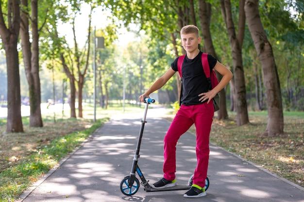 Außenporträt des jungen glücklichen jugendlichen jungen, der einen roller auf natürlicher oberfläche reitet