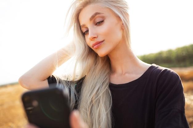 Außenporträt des jungen hübschen blonden mädchens, das selfie mit dem smartphone nimmt.