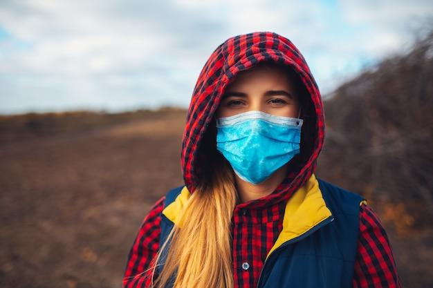 Außenporträt des jungen mädchens mit der medizinischen gesichtsmaske gegen viren. prävention von coronavirus und covid-19.
