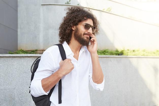 Außenporträt des jungen mannes mit lockigem haar und üppigem bart, der die straße entlang geht, während mit telefon telefonierend, weißes hemd und schwarzen rucksack tragend