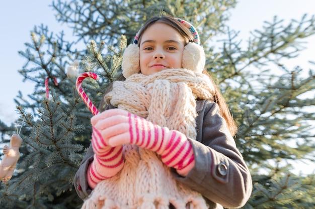 Außenporträt des kleinen mädchens nahe dem weihnachtsbaum