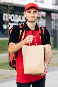 Außenporträt des lieferers mit roter uniform, die lebensmitteltüten hält, die auf den kunden warten