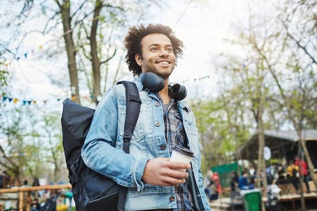 Außenporträt des modischen afroamerikanischen mannes mit afro-haarschnitt, jeansmantel und rucksack tragend, während kaffee halten und beiseite schauen, im park gehen oder auf jemanden warten.