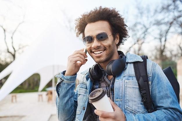 Außenporträt des modischen attraktiven dunkelhäutigen mannes mit afro-frisur, die kopfhörer über hals trägt, auf smartphone spricht und kaffee trinkt, während in stadt mit rucksack spazieren geht.