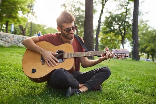 Außenporträt des schönen lächelnden hipster-mannes, der auf gras im park sitzt und gitarre spielt