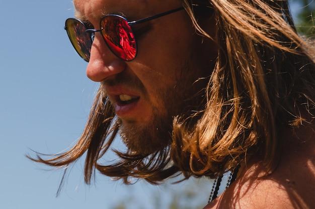 Außenporträt des sexy hemdlosen langhaarigen jungen mannes in der roten sonnenbrille.