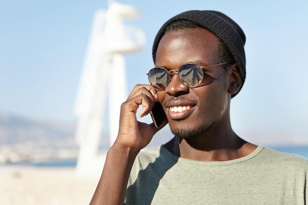 Außenporträt des sorglosen glücklichen jungen mannes, der auf handy mit freund spricht
