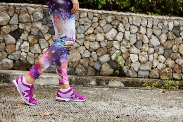 Außenporträt des weiblichen läufers mit fit athletischen beinen, die lila turnschuhe tragen, die entlang des betonweges im stadtpark gehen und nach intensivem training den atem anhalten und sich auf den marathon vorbereiten