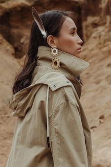 Außenporträt einer atemberaubenden jungen frau im profil, die einen trenchcoat mit einer feder im haar trägt.
