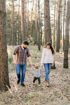 Außenporträt einer glücklichen familie von drei personen, mutter, vater, kleiner kleinkindjunge, die draußen in den schönen kiefernwald an einem herbsttag gehen