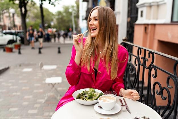 Außenporträt einer hübschen, stilvollen blonden frau, die ihre gesunde vegetarische schüssel auf der stadtterrasse genießt, leckeres mittagessen, stilvolle kleidung.