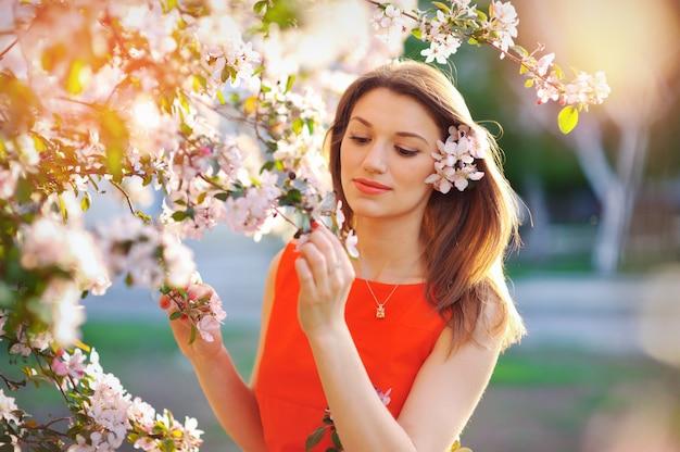 Außenporträt einer schönen brünetten frau im blauen kleid unter blühenden apfelbäumen