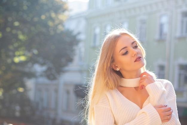 Außenporträt eines großartigen modells mit stilvollem outfit, das auf der straße mit natürlichem sonnenlicht posiert. freiraum