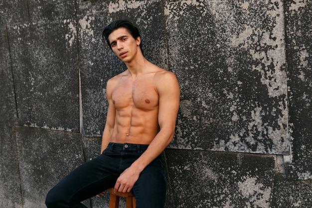 Außenporträt eines gut aussehenden jungen mannes mit heißer passform mit muskulösem körper und nacktem oberkörper, der sixpack-bauchmuskeln zeigt, die an der alten schwarzen wand aufwerfen.