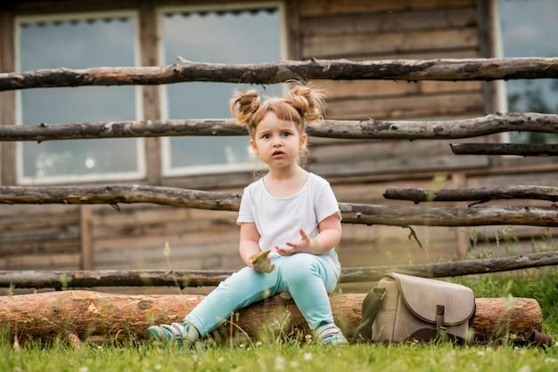 Außenporträt eines mädchens, das auf dem gras nahe dem zaun sitzt. sommer im dorf. schönes baby auf einer holzbank. ökologie und glückliche kindheit.