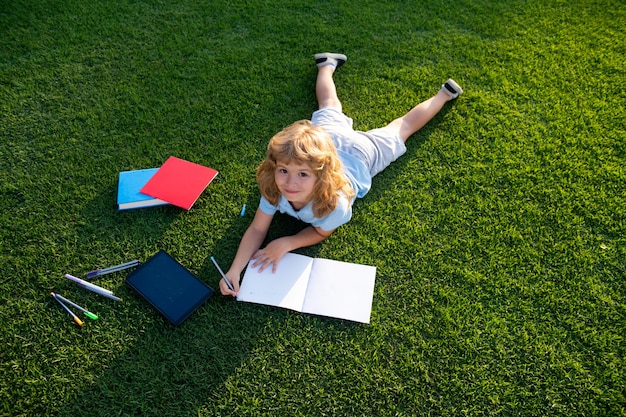 Außenporträt eines netten jungen kleinen jungen, der auf notizbuch schreibt. zurück zur schule. kindererziehung. beginn des schulunterrichts. hausaufgaben im sommerurlaub. vorschulstudent im freien.