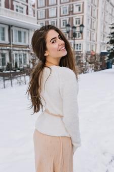 Außenporträt von der rückseite der reizenden frau im romantischen outfit, das im wintertag auf schnee aufwirft. foto des reizenden europäischen weiblichen modells, das über schulter während des spaziergangs in kaltem wetter schaut.