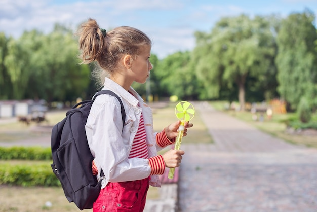 Außenporträt von zehnjährigem blondem kindergir, park, himmel im wolkenhintergrund, kopienraum