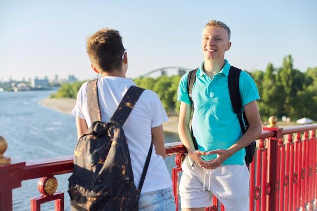 Außenporträt von zwei befreundeten teenagerjungen 15, 16 jahre alt, lachend, sprechend am sonnigen tag, stehend auf der brücke über den fluss. urbaner lifestyle, teens, freundschaft, kommunikation