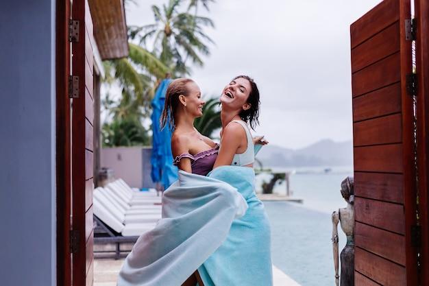 Außenporträt von zwei glücklichen frau in bikinis mit strandtüchern im urlaub außerhalb der villa durch schwimmbad am regnerischen tag
