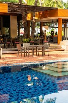 Außenterrassentisch und -stuhl rund um den pool